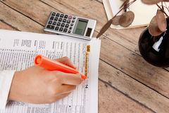 Business woman filling form 1040. Business woman filing federal income tax form 1040 Stock Photo