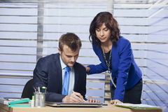 Business woman flirting with a man in the office. Smiling young business women flirting with a men in the office royalty free stock photo