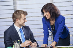 Business woman flirting with a man in the office. Smiling young business women flirting with a men in the office stock images