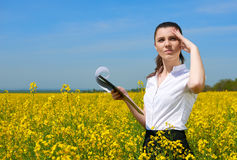 Business woman in flower field outdoor with clipboard look into the distance. Young girl in yellow rapeseed field. Beautiful sprin Royalty Free Stock Photo