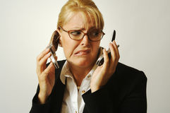 Business Woman Flustered. Business woman expresses her frustration as she shuffles two cell phones Royalty Free Stock Images
