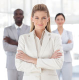 Business woman with folded arms. Young Business woman with folded arms in front of associates royalty free stock photo