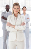Business woman with folded arms with associates Stock Photography