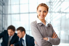 Business Woman With Folded Hands. Young businesswoman standing with folded hands, her colleagues at the background Stock Photo