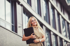 Business woman with folder. Successful beautiful young business woman standing against a background of buildings with folder Stock Image
