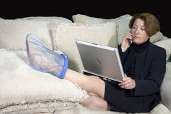 Business Woman with Foot Injury Royalty Free Stock Image
