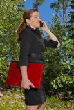 Business woman in the forest on her cell phone. Royalty Free Stock Photos