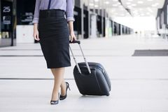 Business woman walking with wheeled bag. Business woman in formal clothing walking with wheeled bag at airport terminal Royalty Free Stock Images