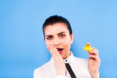 Business woman in formal wear on blue background. Young beautiful woman on office outfitt with a duck in her hands , on blue background stock photo