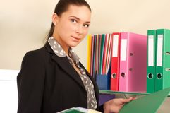 Business woman in front of shelves with folders Stock Photography