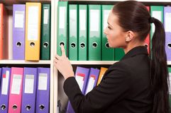Business woman in front of shelves with folders Royalty Free Stock Photos