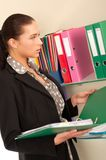 Business woman in front of shelves with folders Royalty Free Stock Image