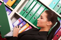 Business woman in front of shelves with folders Royalty Free Stock Photo