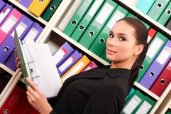 Business woman in front of shelves with folders Royalty Free Stock Images