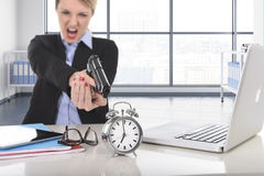 Business woman furious and angry working with computer laptop pointing gun to alarm clock Stock Photos