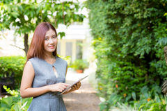 Business woman in the garden looking tablet. Business woman in the garden looking tablet - happy and smiling Stock Image