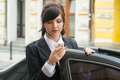 Business-woman gets into the car and holds cell phone Royalty Free Stock Image