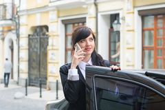 Business-woman gets into the car and talks on cell phone Royalty Free Stock Images