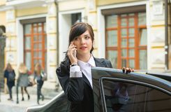 Business-woman gets into the car and talks on cell phone Royalty Free Stock Photo