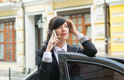 Business-woman gets into the car and talks on cell phone Royalty Free Stock Photos