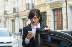 Business-woman gets into the car and talks on cell phone Royalty Free Stock Image