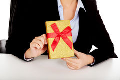 Business woman with gift box sitting behind the desk Royalty Free Stock Image