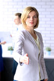 Business woman giving a handshake  during meeting with business people Royalty Free Stock Image