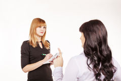 Business woman giving instructions to her secretary in the offic Royalty Free Stock Image