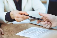 Business woman giving pen to businessman ready to sign contract. Success communication at meeting or negotiation.  royalty free stock photography
