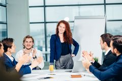Business woman giving presentation to colleagues in office. Businesswoman showing project on flipchart while giving presentation to colleagues in office Royalty Free Stock Photography