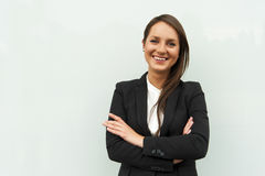 Business woman by the glass wall in the city smiling at camera. Stock Photography