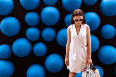 Business woman in glasses on abstract background. Beautiful girl in a dress on a background of blue balls Stock Images