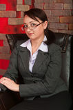 Business woman in glasses in armchair royalty free stock photo