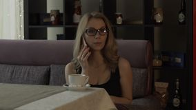 Business woman in glasses calling by mobile phone during coffee break. Business woman in glasses calling by mobile phone on background coffee cup at table in stock video