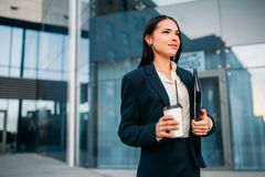 Business woman in glasses with coffee in hands. Against skyscraper. Modern building, financial center, cityscape. Successful female businessperson Royalty Free Stock Image