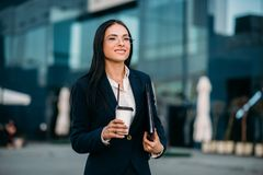 Business woman in glasses with coffee in hands. Against skyscraper. Modern building, financial center, cityscape. Successful female businessperson Stock Photos