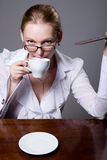 Business woman in glasses with a cup of coffee and a chocolate b Royalty Free Stock Photos