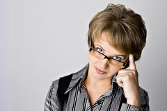 The business woman in glasses is dissatisfied. On a gray background stock photo