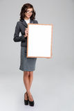 Business woman in glasses holding blank board. Full lenght portrait of business woman in glasses and gray suit holding blank board royalty free stock photo