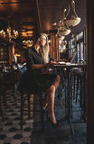 Business woman in glasses indoor with coffee and laptop taking notes in restaurant Stock Photo