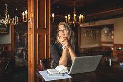 Business woman in glasses indoor with coffee and laptop taking notes in restaurant. Business woman indoor with coffee and laptop taking notes in restaurant at Stock Photo