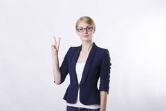 Business woman with glasses in jacket showing two fingers Royalty Free Stock Images