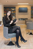 Business woman in glasses sits on a chair Stock Photo