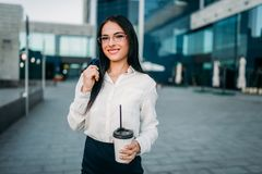 Business woman in glasses, suit and coffee in hand. Modern building, financial center, cityscape. Successful female businessperson Stock Images