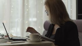 Business woman in glasses typing on keyboard notebook sitting at couch in cafe. With coffee cup. Beautiful woman working on wireless laptop during business stock video footage