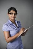 Business Woman with glasses writing on clipboard Royalty Free Stock Images