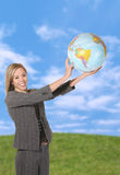 Business Woman with Globe. A pretty business woman holding the globe in the sky royalty free stock image