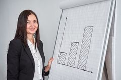 Business woman with graph in office, pointing at the diagram royalty free stock photos