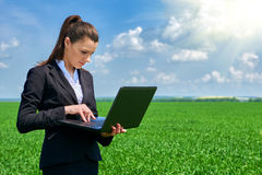 Business woman in green grass field outdoor work on laptop. Young girl dressed in black suit. Beautiful spring landscape with clou Royalty Free Stock Images