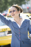 Business Woman Hailing A Cab. Beautiful businesswoman hailing a cab on sunny day Stock Images